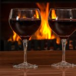 two glasses of red wine by the fireplace